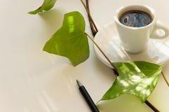 启发咖啡时间 有新鲜的绿色叶子的加奶咖啡杯子和在白色背景的一支文本的笔和空间 免版税图库摄影