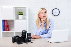 启发概念-有照相机、计算机和摄影设备的妇女专业摄影师考虑某事的 库存图片