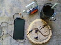 吸尘在切除树、智能手机和一个杯子的耳机无奶咖啡 库存图片