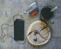吸尘在切除树、智能手机和一个杯子的耳机无奶咖啡 免版税库存图片