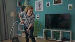 吸尘她的舒适公寓的年轻美女手扶的射击 股票视频