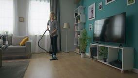 吸尘她的舒适客厅的年轻美女手扶的射击 股票视频