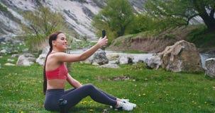 吸引人与在一种坚硬锻炼以后在自然走通过草的完善的身体夫人坐下和享用 影视素材