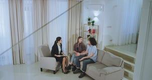 吸引人和微笑的夫妇有与他们的不动产房地产经纪商的一个任命在一个现代宽敞房子他们聊天 股票录像