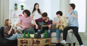吸引人多种族朋友在一家大公司中有了不起的时光演奏在吉他他们dacing的某些人和 股票视频