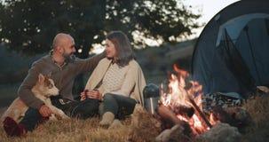 吸引人年轻夫妇有浪漫时光在自然中间在除营火以外的晚上他们放松 影视素材