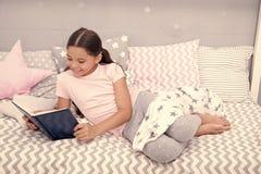 吸引人的故事 女孩儿童与枕头的位置床读了书 孩子准备上床 平衡迷住的时刻 库存图片