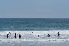 吸引由巨大的人群在祖马海滩在马利布,加利福尼亚,在阵亡将士纪念日,海豚小荚得到接近t 免版税库存照片