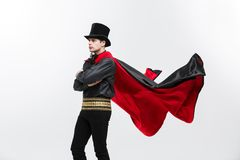 吸血鬼万圣夜概念-振翼英俊的白种人吸血鬼万圣夜的服装画象他的红色,黑斗篷 免版税库存照片