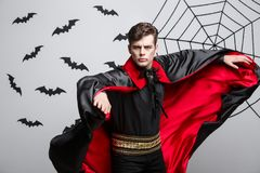吸血鬼万圣夜概念-振翼英俊的白种人吸血鬼万圣夜的服装画象他的红色,黑斗篷 图库摄影