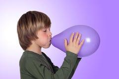 吹一个紫色气球的可爱的青春期前的男孩 免版税库存照片