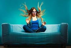 吹与在长沙发的片剂的女孩头发 免版税库存照片