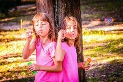 吹与鞭子的小女孩泡影在公园 免版税库存图片