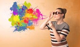 吹五颜六色的飞溅街道画的逗人喜爱的女孩 图库摄影