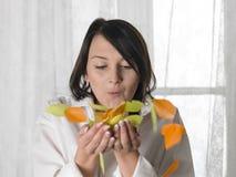 吹五颜六色的鸟羽毛的年轻逗人喜爱的女孩 免版税库存图片