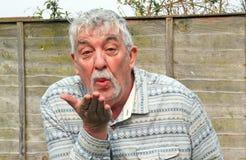 吹亲吻特写镜头的老人。 免版税库存图片