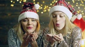 吹从手的新年的帽子的女孩雪 从手的吹的雪 新年心情的概念 迷人的冬天 股票视频