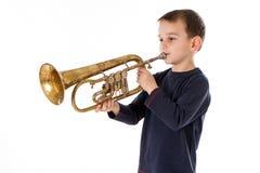 吹入喇叭的男孩反对白色背景 免版税库存照片