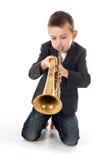 吹入喇叭的男孩反对白色背景 图库摄影