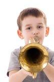 吹入喇叭的年轻男孩 免版税库存照片