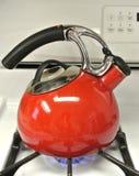 吹口哨在火炉顶面开水的红色搪瓷茶壶 库存照片