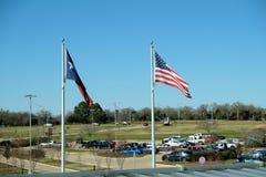 吹在一个停车场的风的得克萨斯和美国国旗 免版税库存照片