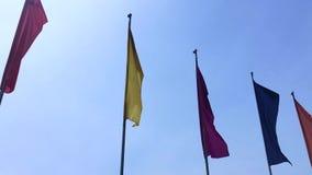 吹在天空蔚蓝背景的风的五颜六色的旗子 影视素材