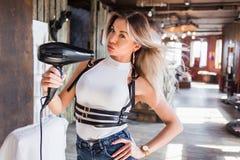 吹在她自己的性感的白肤金发的妇女一个吹风器,特写镜头 头发,生活方式,发型,发廊概念 免版税图库摄影