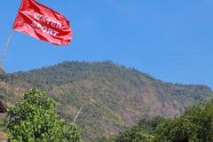 吹在沿海红旗的风的警告的红旗在距离和天蓝色的天空蔚蓝的竹帆柱小山 免版税库存照片