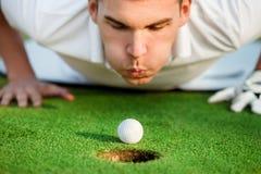 吹在球的高尔夫球运动员 图库摄影