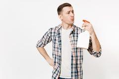 吹在白色有擦净剂液体的空白空的清洗的浪花瓶被隔绝的方格的衬衣的年轻管家人 免版税库存照片