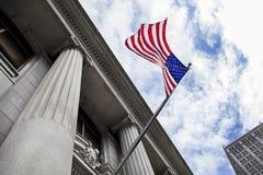 吹在石专栏修造前面的风的美国国旗与天空和云彩在背景中 免版税库存照片