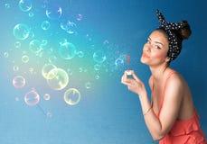吹在蓝色背景的俏丽的夫人五颜六色的泡影 免版税库存图片