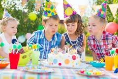 吹在蛋糕的孩子蜡烛在生日聚会 免版税库存图片
