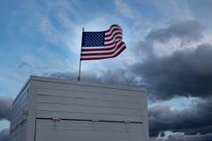 吹在风的美国国旗在南海滩,迈阿密的一个海滩小屋顶部;行动造成的被弄脏的旗子 图库摄影
