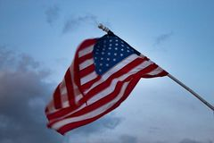 吹在风的美国国旗:行动造成的被弄脏的旗子 库存照片