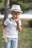 吹在他的手指的体贴的孩子 有一个棒棒糖的男孩在绿色公园背景 户外一个逗人喜爱的男孩在夏天 免版税库存图片
