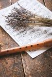 吹奏与笔记和淡紫色在木桌垂直 免版税库存照片