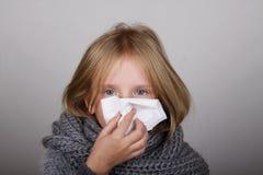 吹她的与纸组织的逗人喜爱的金发女孩鼻子 儿童冬天流感过敏医疗保健概念 免版税库存图片