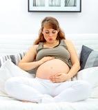 吹她的亲吻孕妇的腹部 免版税图库摄影