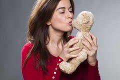 吹她的爱拥抱玩具的更老的可爱的夫人亲吻 图库摄影