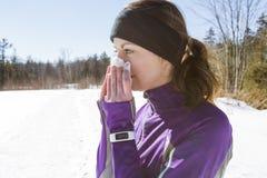 吹她的鼻子外面在寒冷的赛跑者妇女 免版税库存照片