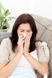 吹她的鼻子病的沙发妇女 库存图片