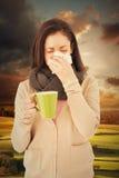 吹她的鼻子的病的妇女的综合图象,当拿着一个绿色杯子时 免版税库存图片