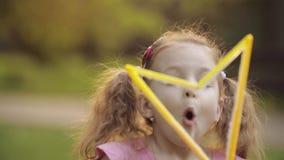 吹巨大的空气肥皂泡吹风机中等特写镜头的确信的嬉戏的矮小的逗人喜爱的女孩 影视素材