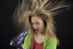 吹干她的头发的女孩 免版税库存图片