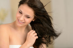 吹干她的头发的年轻微笑的女孩 免版税库存图片