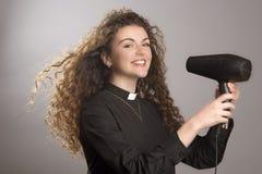 吹干她长的头发的年轻教区牧师 免版税库存照片