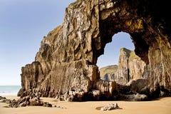 吹形成在彭布罗克角海岸线下的孔一个岩石拱道在Lydstep和Manorbier海湾之间 库存图片