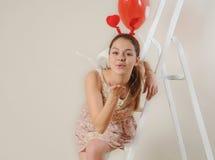 吹您的逗人喜爱的美丽的天使女孩亲吻 图库摄影